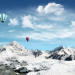 Mountain landscape with snow and stream and hot air balloon flyi — Stock Photo