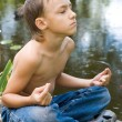Young little boy meditating — Foto de stock #10934342