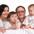A happy family of four in the white jerseys on a bed - Stock Photo