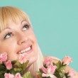 Portrait of a beautiful blonde Caucasian smile lady with flowers — Stock Photo #10939509