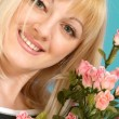 Portrait of a beautiful blonde Caucasian nice lady with flowers — Stock Photo