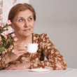 A beautiful older lady sitting at a table — Stock Photo