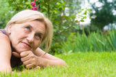 Old woman on grass — Stock Photo