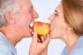 Old couple with apple — Stock Photo