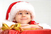 A little youngster sits with a gift — Stock Photo