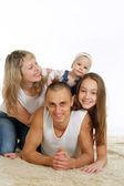 Happy family of four lying — Stock Photo