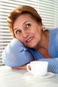 An elderly woman sits at a table — Stock Photo