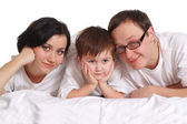 Family of three in white shirts on the bed — Stock Photo