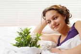 A beautiful caucasian gladness girl in bed with a bouquet of flo — Stock Photo