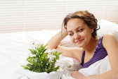 A beautiful caucasian woman in bed with a bouquet of flowers — Stock Photo