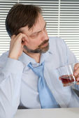 Problems businessman sitting at a table with a bottle — Stock Photo