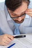Un uomo d'affari sta valutando una lente di ingrandimento — Foto Stock
