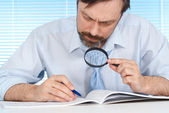 A business man is considering a magnifying glass — 图库照片
