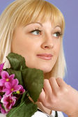 Portrait of a beautiful nice blonde Caucasian female with flower — Stock Photo