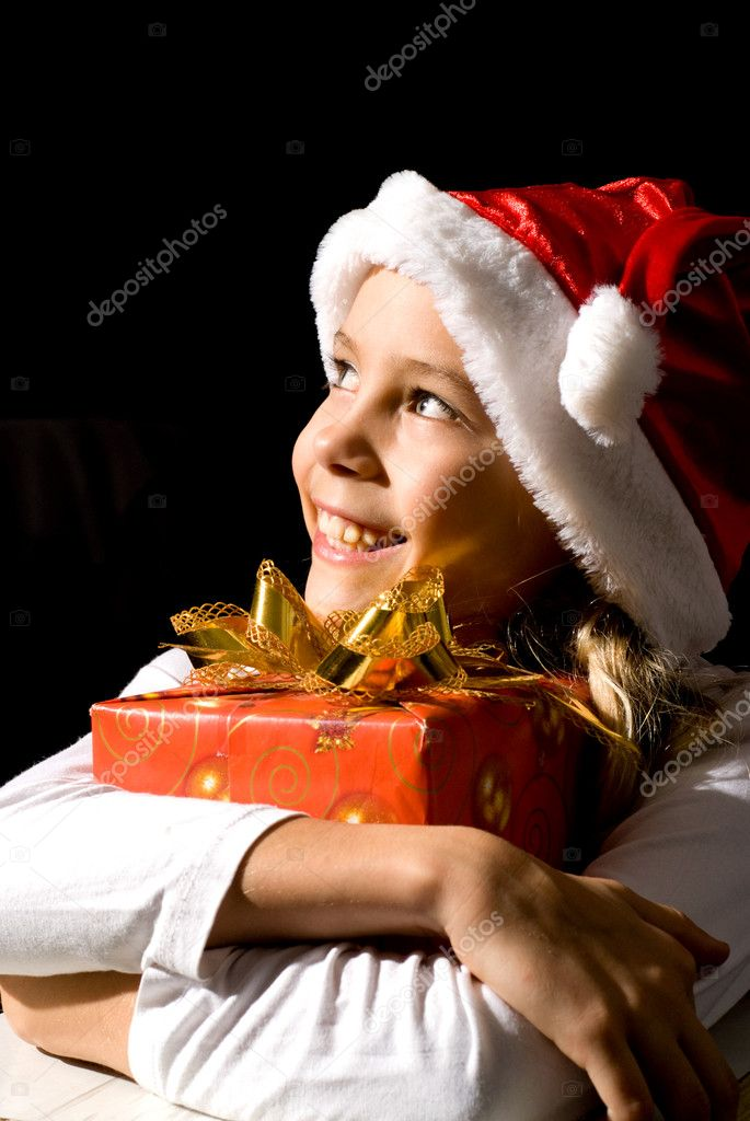 Little girl in red santa hat with present on a black background — Stock Photo #10934447