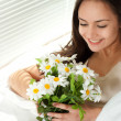 Young Caucasian woman sitting in bed with flowers — Stock Photo #10940178