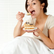 Young Caucasian female sitting in bed with a cake — Stock Photo #10940185