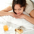Young Caucasian woman lying in bed with cake and juice — Stock Photo #10940189
