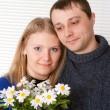 Happy Caucasian couple with flowers stands — Stock Photo