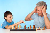 Happy Caucasian grandfather with his grandson plays chess agains — Stock Photo