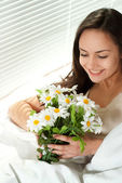 Young Caucasian woman sitting in bed with flowers — Stock Photo