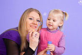 Pretty Caucasian mama with her daughter let the bubbles — Stock Photo