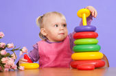 A small charming Caucasian tot sitting at the table and plays wi — Stock Photo