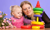 Pretty Caucasian mama with her daughter play with a pyramid — Stock Photo