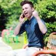Happy young man on telephone — Stock Photo