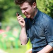 Young man angry on telephone in the park — Stock Photo