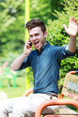 Very happy man at telephone in park — Photo