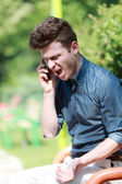 Young man angry on telephone — Stock Photo