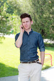 Unhappy man in park on telephone — Stock Photo