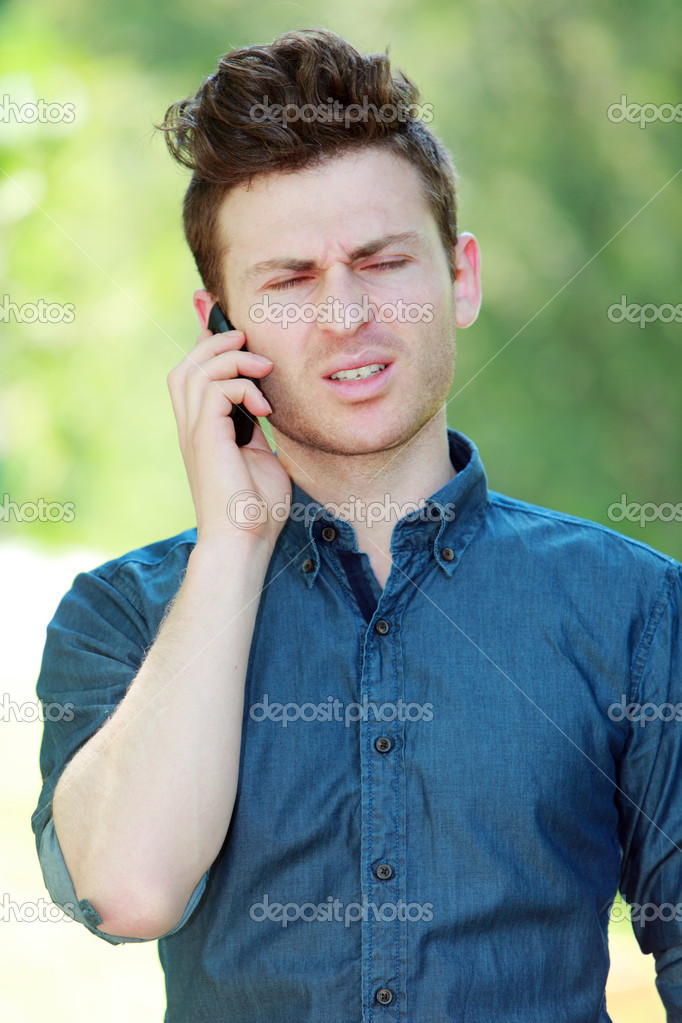 Disappointed young red hair man at telephone  Stock Photo #11149553