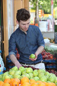 Young customer choosing fruits at grocery — Stock Photo