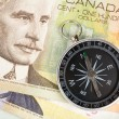 Compass and canadian dollar - Stock Photo