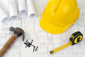 Yellow hard hat and heap of project drawings — Stock Photo