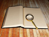 Open book and a magnifying glass — Stock Photo