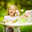 Little blonde playing in the spring garden — Stock Photo