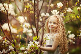 Beautiful girl and blooming magnolia tree — Stock Photo