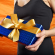 Stock Photo: Black dressed woman blue gift