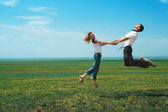 Fun couple in jump on the field — Stock Photo