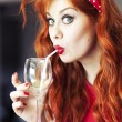 Stock Photo: Funny girl drinking wine using straw.