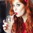Funny girl drinking wine using straw. — Stock Photo