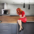 Pensive woman in a kitchen — Stock Photo