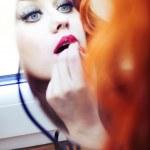 Beautiful redhead puts make up on. — Stock Photo