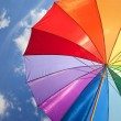 Rainbow umbrella on sky background — Stockfoto
