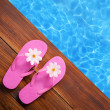 Holiday concept, flip flops a the pool - 图库照片