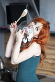 Ama de casa hermosa lamiendo una cubierta del pote — Foto de Stock