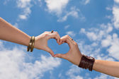 Hands as a hart shape on a cloudy sky - love concept — Foto Stock